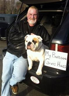 """Michael Cragin (retired special education teacher) with his 15-month-old English bulldog, Truman. Cragin's dog is giving out free hugs as a way to help the community heal from the school shooting tragedy at Newtown, Conn. Cragin, 63, and Truman, 15 months, came down to the local Dunkin' Donuts shop, where he opened up the hatch of his SUV and posted a handwritten sign: """"My bulldog gives hugs."""""""