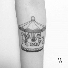 Fine line carousel tattoo on the inner forearm.