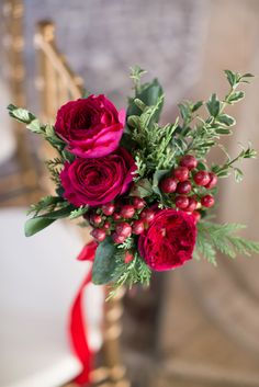 The combined warm, red and raspberry tones of David Austin Roses' Tess and Darcey #weddingroses work together to create a #floraldecor piece for guest chairs along the matrimony aisle.