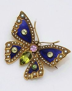 An early 20th century gold mounted enamel and gem set butterfly brooch The thoraz of pink sapphire, the abdomen set with a pear-cut peridot, between blue enamelled wings and peridot highlights, the wings edged with half pearls, with diamond set eyes, length 3.2cm.