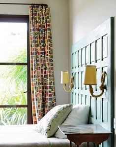 Rustic bedroom with patterned curtains and green headboard