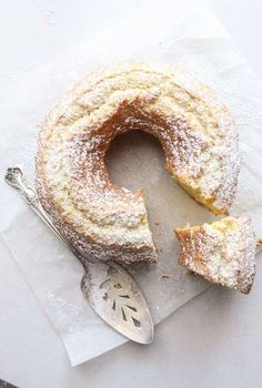 Italian lemon cake dusted with powdered sugar on a white board with a slice cut and a silver serving spoon