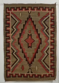 Southwest Weaving, Navajo, c. first quarter 20th century, woven with natural and synthetic dyed homespun wool, multicolored geometric design with meandering border on a variegated brown background, 87 x 60 in.