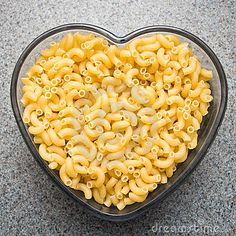 Dry macaroni style noodles in a heart shape dish.