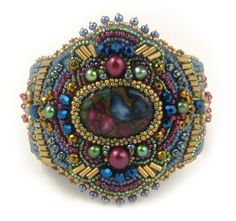 In this bead embroidery bracelet kit the jewel tones of the focal composite jasper stone and matching button are reflected in the pearls, seed beads, crystals and bugle beads used in the embellishment