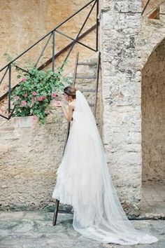 Bride with cathedral length veil on a ladder in Italy
