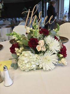 Centerpiece with burgundy carnations, white spider mums, cream spray roses, snap dragons, eucalyptus, and babies breath.