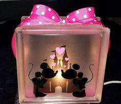 Este bloque de cristal de MICKEY & MINNIE MOUSE besos es la perfecta luz de noche o decoración!!!!!!  Se hace con un solo bulbo de luz con un interruptor on/off, Mickey, Minnie y Castillo y lunares de la cinta de vinilo. Disponible en color rosa o rojo. Esta luz mide aproximadamente 8 x 8 x 3 pulgadas.  ¿Qué fan de Disney no ama a esta linda lamparita de Mickey y Minnie?  DESCARGO DE RESPONSABILIDAD: Los artículos vendidos por BlockDecor no son productos con licencia Disney, NFL, MLB, NBA…