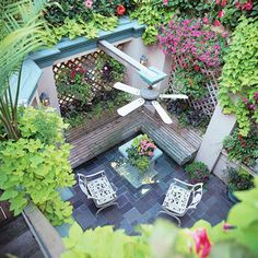 This slate-covered patio enjoys a luxurious sense of seclusion thanks to prolific vines and flowers climbing its lattice walls.
