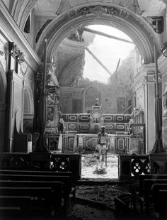 Pvt. Paul Oglesby of the U.S. 30th Infantry Regiment stands in reverence before the altar in a bomb-damaged Catholic church. Acerno, Salerno province,Italy. 23 September 1943.
