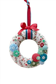 How to make a festive wreath that's fresh and colourful. Cover a polystyrene ring with fabric of your choice, then embellish with yoyos topped with buttons. Your door will look all the more glam and inviting to arriving guests.