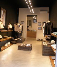 Lojas com iluminação central através de spots para destaque e contraste com temperatura de cor confortável.