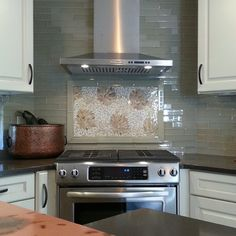 Art of Design, glass tile decorative backsplash, copper accents, and creamy white cabinets.