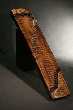 Yatga (Zither) – The yatga is a half-tube zither with a movable bridge. It is constructed as a box with a convex surface and an end bent towards the ground. The strings are plucked and the sound is very smooth. The instrument was considered to be sacrosanct and playing it was a rite, bound by taboos. The instrument was mainly used at court and in monasteries, since strings symbolised the 12 levels of the palace hierarchy.