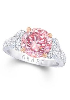 Graff engagement ring set with a round Fancy Vivid purple pink diamond with white diamonds on the shoulders.