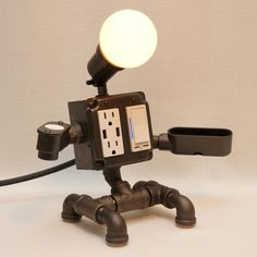 Robot Steampunk Industrial Pipe Desk Lamp with Dimmer, 2 AC & 2 USB outlets, Smartphone Charging Cradle, optional Apple Watch Charger AirBnB Industrial Pipe Desk, Industrial Robots, Industrial Lighting, Vintage Lighting, Desk Lamp, Table Lamp, Lampe Tube, Handmade Lamps, Handmade Table