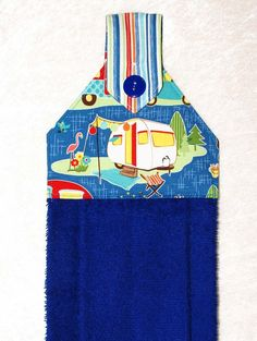 A blue hand towel with cheerful camper, flamingo and stripes. The plush blue towel is more luxurious than a standard kitchen towel. Featuring a designer fabric with a travel trailer on blue and charming blue striped fabric, it is sure to add fun to your home or camper kitchen and bath.  This handmade hanging towel works well buttoned over the handle of stove, dishwasher, drawer pull, or even a knob, door knob or vertical handle with optional hanging ring. It can even be used over a towel bar…