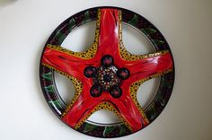 ZiegenBock Star, is a bright red star flower loaded with splashy embellishments and ZiegenBock bottlecaps. It is actually a wheelcover thats been rescued from the side of the road and given a 2nd life. Brightly painted with a decorative leaf border, this eco-friendly wall art is bound to add a splash of color to any room! ZiegenBock Star is 15 1/2 in diameter and has been thoroughly cleaned and degreased -the very messy unfun part! The wheel cover is then primed, coated with many layers of…