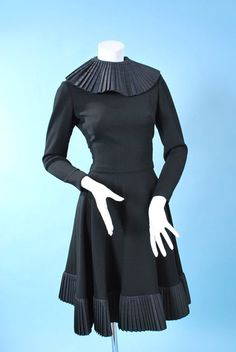 Geoffrey Beene and dating to the third quarter of the 20th century. Made in a fine couture quality wool with nice drape, back zipper, fitted bodice, long sleeves, full bias cut skirt, lined in silk with whimsical silk box pleat collar with these same pleats repeated at hem. In excellent condition, probably use to be worn with belt.