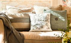Cojines en blanco, marrones y grises sobre sofá beige