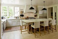Keeping materials simple and neutral.  Love the island as a new take on the kitchen table.  Lighting, light wood floors, and rustic island base keeps it casual and 'farmhouse'.  Also, no upper cabinets on the two walls keep it light and bright.