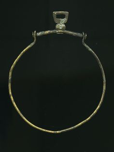 Purse frame (London Museum Type B4), incomplete. It has one pendent frame missing. It is chevron shaped, quite slender and spherical in section, with flat disc terminals. The pendent frame is spherical in section and it has no central boss. The metal frame is usually the only surviving part of a medieval purse. Production Date: Late Medieval; 14th-15th century