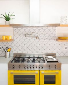 Charmant White And Yellow Kitchen Features A Stainless Steel Hood, Flanked By  Stacked Blond Wood Floating Shelves, Placed Over A Satin Nickel Pot Filler  Lining A ...