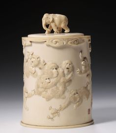 A beautifully carved Japanese ivory tusk vase in the round with a group of monkeys being attacked by an eagle, the lid surmounted with a walking elephant.