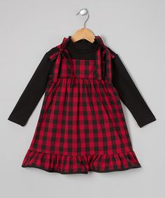 Playful plaid meets a classic jumper-style silhouette in this fun frock. A layered look, ribbon-tie shoulders and kicky ruffles at the hem lend this staple timeless girly charm that pairs perfectly with tights and spunky pigtails.