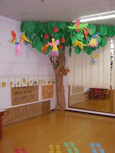 These paper birds and trees compliment the children's art center which is shown on the wall underneath. The mirror reflects all the colors in the room and the colorful foot prints center on the paper tree.