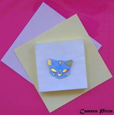 Spilla a forma di testa di gatto. Lamina plastica monocromata e brillantini, su supporto metallico; cm 3 x 3,5.  http://www.ebay.it/usr/camerapicta-art