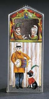 A Victorian vesta case sold in 1999 at Christies for $12,429. The front is enameled with a seaside Punch and Judy tent. It shows Mr. Punch, Judy, Toby the Dog and a drummer, by Sampson Mordan, London 1887.