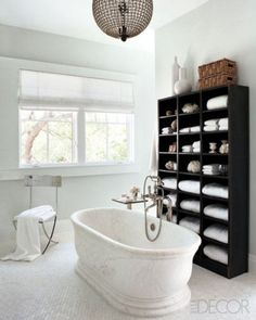 An Urban Archaeology tub, a Waterworks tub filler, and an early-20th-century French steel bookcase in the master bath of a Tampa, Florida, home designed by Nate Berkus; the 1940s chandelier is by Lobmeyr, and the walls are painted in Benjamin Moore's Paper White. See the entire home tour