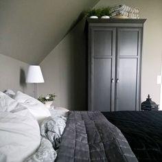 Vanha korkea puinen musta kaappi tuo makuuhuoneen sisustukseen eleganttia ilmettä ja sitoo tilan harmaan sävyt yhteen.