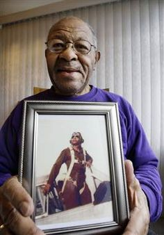George Hickman holds a photo of himself in the cockpit of an AT6 trainer airplane on Jan. 16, 2009. Hickman, one of the original Tuskegee Airmen, died Aug. 19, 2012. (Elaine Thompson / AP file)
