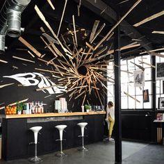 Il y a quelques mois, nous vous présentions le travail de l'artiste suisse Cyril Vouilloz aka Rylsee. Il signe, en collaboration avec l'artiste français Thomas Broquet aka Brokovich, une magnifique installation chez Ride The Wall à Genève. Comme son nom l'indique, l'installation réalisée à l'aide de planches de bois suspendues à des fils crée un vortex étonnant et très graphique grâce au noir des murs de la pièce et de l'utilisation d'un bois clair.