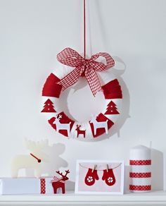 Wrap a polystyrene ring with yarn in red and white – the thicker the yarn, the quicker it is. Decorate with stick-on reindeers and trees! #ChristmasCraft #Wreath