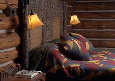 Two shade wall sconces hand over end tables on both sides of a bed in a rustic cabin.