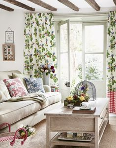 This room is so light and airy - it makes us think of summer! The strawberry-patterned curtains, along with fresh flowers and neutral furniture give the ideal country finish.