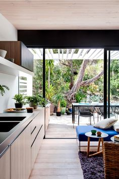 """Exfoliated granite benchtop and timber veneer cupboards in the kitchen create a naturally sleek profile. The 'Vela' outdoor chairs are from [Space](http://www.spacefurniture.com.au/