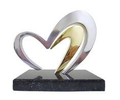 Troféu Coração Peça: bidimensional, 14cm de altura.  Materiais disponíveis: alumínio (prata) ou bronze (dourado ou patinado). Base: madeira natural ipê ou madeira revestida de fórmica preta, 17x10x2cm. Placa cortesia: aço inox (prata) ou latão (dourada), 7x2cm.