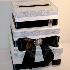 "A classic Wedding Card Reception Box - beautiful 3 tier box with ""bling""and black satin ribbon against a white glittered background. A bow cascades down the front with pearl and rhinestone pendant in Wedding Cake Boxes, Card Box Wedding, Wedding Favors, Wedding Gifts, Wedding Decorations, Wedding Centerpieces, Wedding Mailbox, Wedding Programs, Wedding Venues"