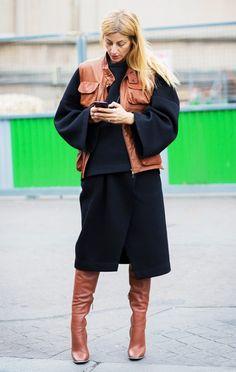 Ada Kokosar wears a black sweatshirt, leather vest, black skirt, and knee-high leather boots