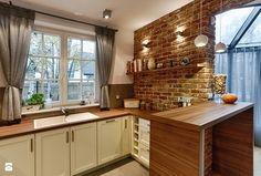 cegła naturalna w kuchni, szare zasłony, białe meble kuchenne, drewniany blat
