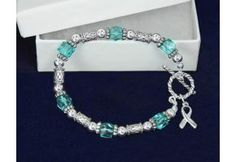 Teal Bead with Silver Ribbon Charm Bracelet. This beautiful teal ribbon stretch bracelet has alternating teal and silver beads all around the bracelet. It has a silver ribbon charm hanging off of it. Very nice for people who don't want a lot of teal on the bracelet. The sterling silver plated bracelets are 8 1/4 inches wide and they stretch to fit any size wrist. Each teal ribbon bracelet comes in a gift box with cotton insert. Sold 18 bracelets per pack. (B-11-3)