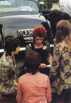 David Bowie signing autographs during the British leg of 1973 Aladdin Sane tour.
