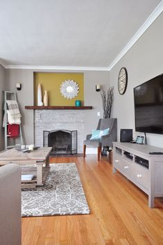 living room with stone fireplace, patterned carpet and flatscreen tv that is hung on the wall