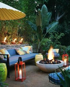 outdoor living: This lush modern oasis has it all, including a beautiful fire pit, streamlined furniture in a jewel tone blue, bursting floral pattern pillows, garden seating in yellow and green and lovely orange lanterns for illuminating a lovely night!