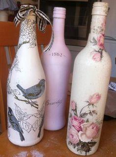 drei flaschen mit servietten mit pinken blumen und grauen vögeln und einem grauen spatz