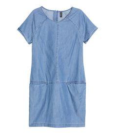 Blau. Kurzes Kleid aus weichem, gewaschenem Denim. Das Kleid hat kurze Raglanärmel mit fixiertem Umschlag und eine Teilungsnaht auf Hüfthöhe. Zwei Taschen